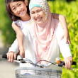 Mother and daughter riding bike — Stock Photo