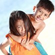 Happy little girl carrying her brother — Stock Photo
