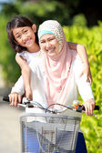 Mother and daughter riding bike — Stockfoto