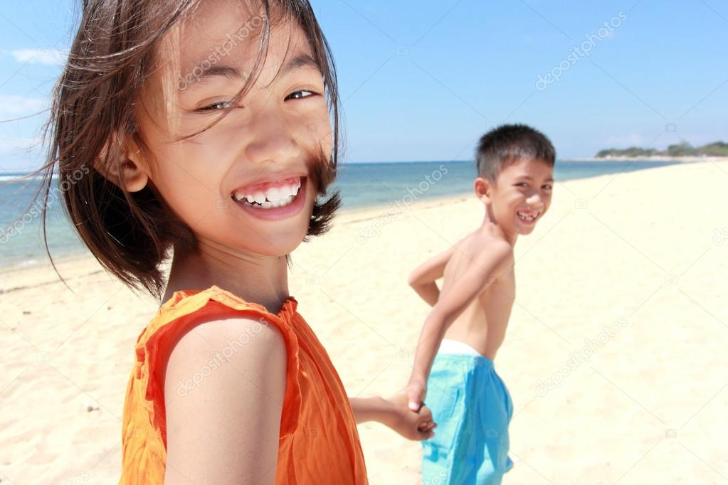 Portrait of happy little boy and girl running in the beach together — Stock Photo #12692017