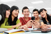 Group of students using mobile phone — Stock Photo