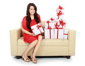 Woman with gift box in the couch — Stockfoto