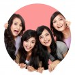 Group of beautiful women smiling peeping through circle hole — Stock Photo