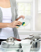 Woman washing dishes in the kitchen — Stock Photo