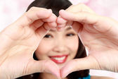 Woman in love showing heart symbol — Stock Photo