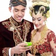 Happy traditional java wedding couple with mobile phone — Stock Photo