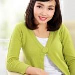 Smiling woman sitting on sofa — Stock Photo
