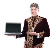 ラップトップを保持しているジャワの伝統的な衣装を身に着けている男します。 — ストック写真