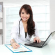 Smiling doctor female working in her office — Stock Photo #27556385