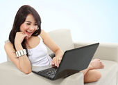 Young woman sitting in sofa using a laptop — Stock Photo
