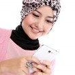 Smiling beautiful muslim woman texting with her smartphone — Stock Photo