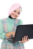 Attractive young woman in head scraf using laptop — ストック写真