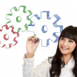Businesswoman drawing gear cogs — Stockfoto
