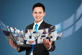 Businessman sharing his photo and video files using laptop — Stock Photo