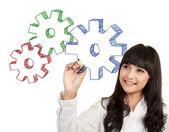 Businesswoman drawing gear cogs — Stockfoto
