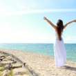 Woman relaxing at the beach with arms open enjoying her freedom — Stock Photo