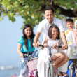 Family with kids enjoy riding bicycle outdoor in the beach — Stock Photo