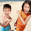 Portrait of happy little boy and girl running in the beach — Stockfoto