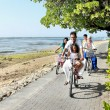 Happy asian family riding bikes in the beautiful morning at the — Stock Photo