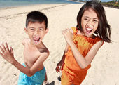 Portrait of happy little boy and girl running in the beach — Stock Photo