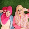 Two muslim woman lying on grass — Foto de Stock