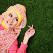 Stock Photo: Young muslim girl lying on grass