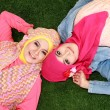 Two muslim woman lying on grass — Stok fotoğraf