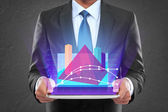 Businessman with tablet pc showing glowing graph triangle shape — Stock Photo
