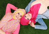 Two muslim woman lying on grass — Stockfoto