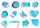 Collection of white torn paper with blue background in many shap — Stockfoto