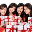 Happy four asian woman with christmas santa hat holding gift box — Stock Photo #34919159