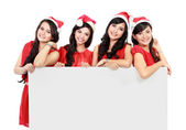 Happy funny people with christmas santa hat holding blank banner — Stock Photo