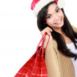 Young woman in santa hat with shopping bag — Stock Photo