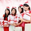 Happy funny people with christmas santa hat holding gift boxes a — Stock Photo #34922805