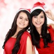 Beautiful two girls in christmas santa hat have fun — Stock Photo