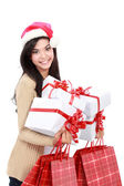 Young woman in christmas hat with shopping bags and gift — Stock fotografie