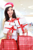 Young woman in christmas hat santa with shopping bags and gift — Stock fotografie