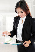 Busy businesswoman open paper and holding clipboard in her offic — Stock Photo