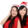 Two girls in christmas santa hat have fun — Stock Photo