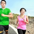 Young couple jogging together on jogging track — Stok fotoğraf