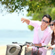 Stock Photo: Young couple with bicycle on the beach