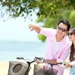 Young couple with bicycle on the beach — Stock Photo #36536801