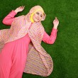 Stock Photo: Young muslim womwearing hijab lying on grass