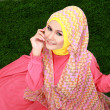Young muslim girl wearing hijab sitting on grass and looking at  — Stock Photo