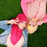 Two beautiful happy muslim woman smiling lying on grass — Zdjęcie stockowe