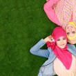 Two beautiful happy muslim woman smiling lying on grass with cop — Stok fotoğraf