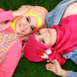 Close up of two beautiful happy muslim woman lying on grass — Stock Photo