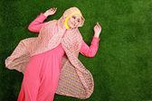 Young muslim woman wearing hijab lying on grass — Stock Photo