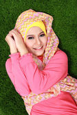 Young muslim girl wearing hijab lying on grass and looking at ca — Stock Photo