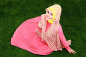 Young muslim girl wearing hijab sitting on grass — Stock Photo